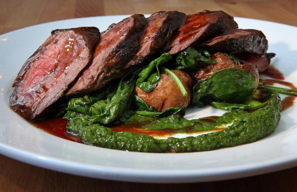 Steak on a bed of wilted spinach.
